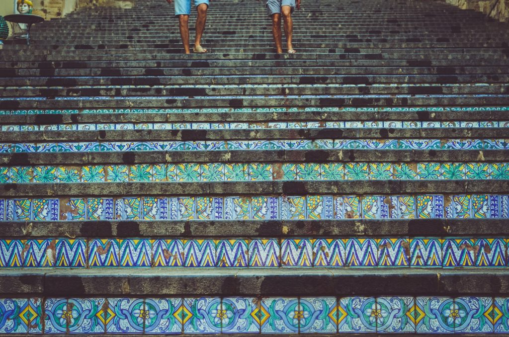 two people walking on stairs that have mosaic tiles on them