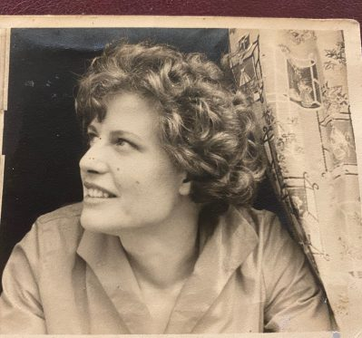 woman with wavy heair looking out of a window