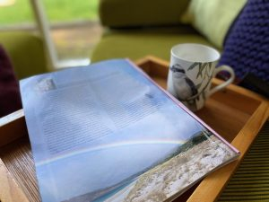 Magazine and tea cup sitting on wooden tray