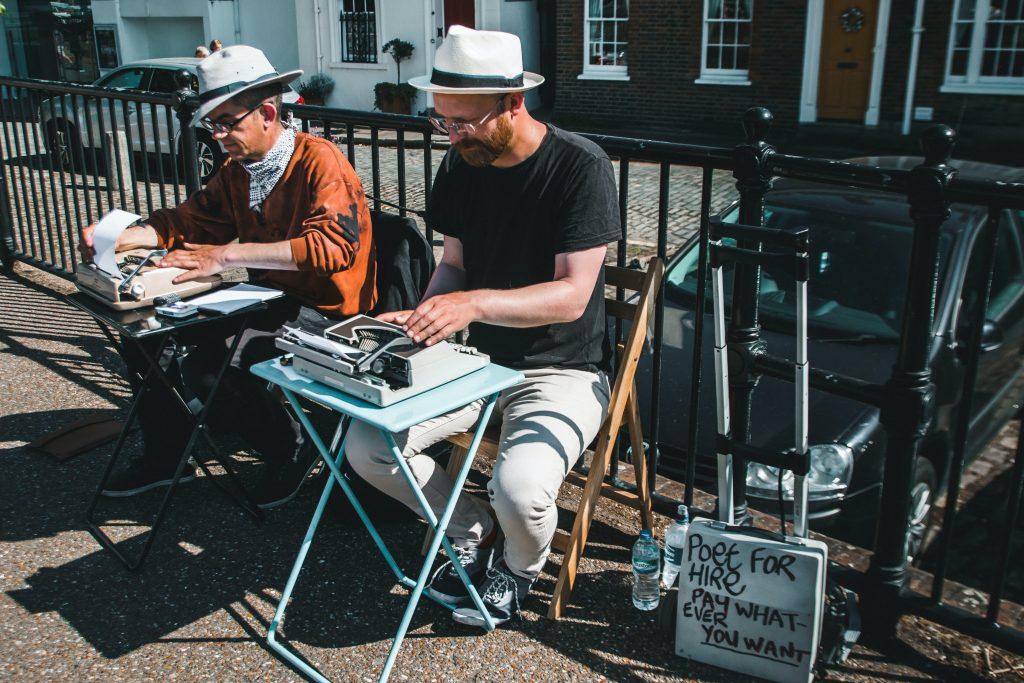 Two men typewriting outdoors