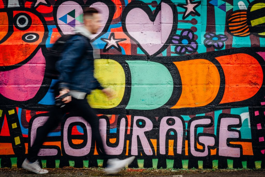 man walking beside grafitti wall with word 'courage'