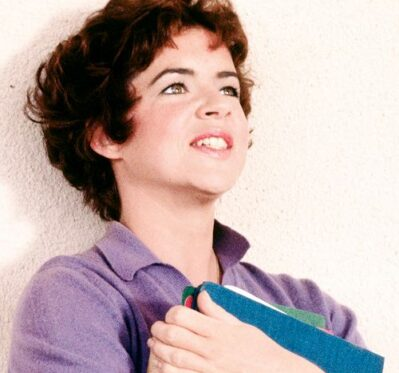 Young woman leans against a wall with school folders in her arms